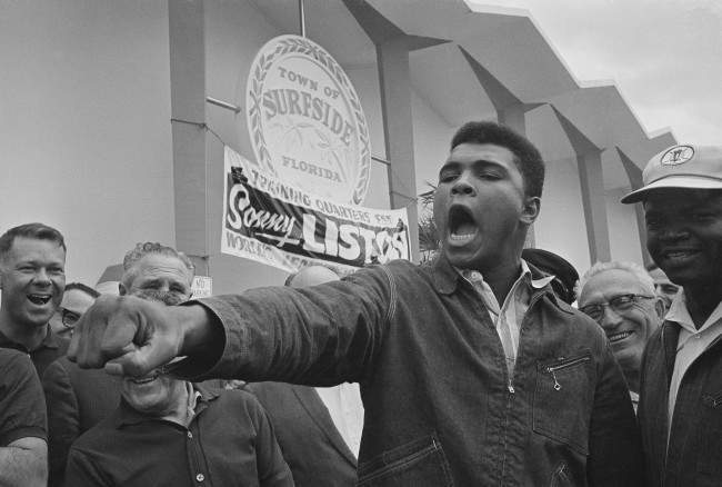 Cassius Clay thrusts his fist out as he describes to a crowd gathered in Surfside, Fla., how he plans to hit champion Sonny Liston in their upcoming bout, in this Feb. 19, 1964 file photo