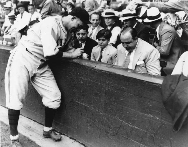 Surrounded by his watchful lieutenants, Chicago's crime boss Al Capone, right, and his 12-year-old son, Al Jr., gets Chicago Cubs' Gabby Hartnett to autograph a baseball just before the Cubs defeated the White Sox, 3-0 on Sept. 9, 1931, in Chicago. Seventy years after Capone's death, the world's most famous gangster still draws a crowd in Chicago and visitors from all over the world come to search for anything Capone. (AP Photo/file)