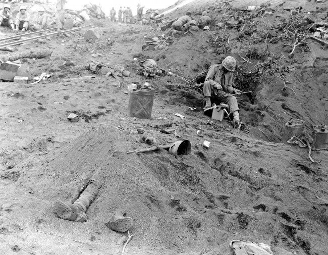 The booted feet of a dead Japanese soldier, foreground, protrude from beneath a mound of earth on Iwo Jima during the American invasion of the Japanese Volcano Island stronghold in 1945 in World War II. U.S. Marines can be seen nearby in foxholes.