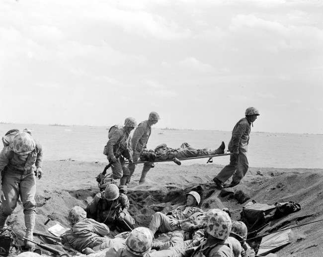 "Corpsmen carry a wounded Marine on a stretcher to an evacuation boat on the beach at Iwo Jima while other Marines huddle in a foxhole during the invasion of the Japanese Volcano Island stronghold in this file photo of Feb. 25, 1945. A search team is on the island looking for a cave where the Marine combat photographer who filmed the famous World War II flag raising 62 years ago is believed to have been killed in battle nine days later, military officials said Friday, June 22, 2007. The team, from the Joint POW/MIA Accounting Command, based at Hickam Air Force Base in Hawaii, is on Iwo Jima looking for the remains of Sgt. Willam H. Genaust and ""as many other American servicemen as they can find,"" JPAC spokesman Lt. Col. Mark Brown told The Associated Press."