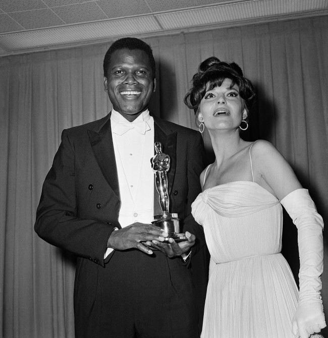 "Sidney Poitier was named best actor of the year for 1964 for his role in ""Lilies of the Field,"" awarded by actress Anne Bancroft, at right, at ceremonies in Santa Monica, Calif. on April 13, 1964. The award was presented by the Motion Picture Academy."