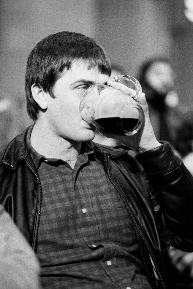 Pop star Mike Oldfield drinking a pint of beer whilst at Abbey Road Studios where there was an auction to sell off the Beatles belongings