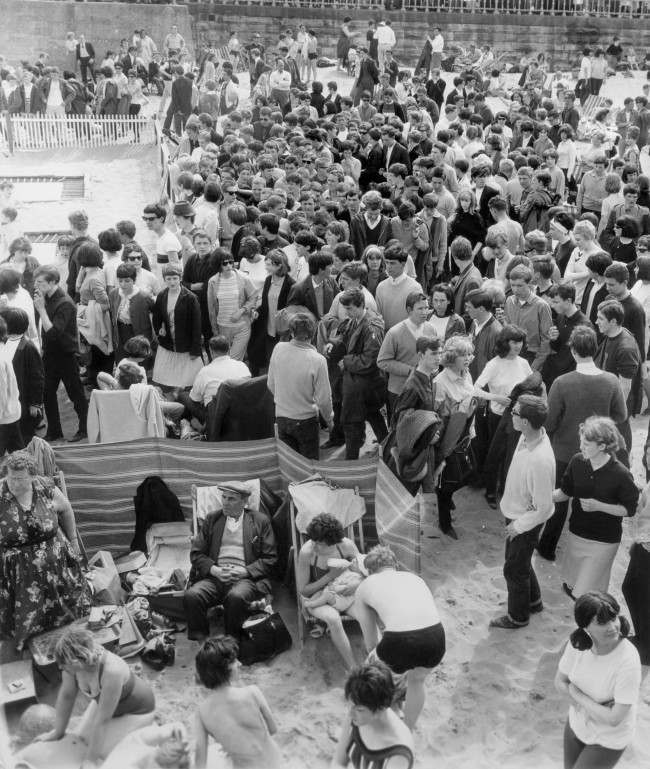 A family shelter behind a windbreak undeterred by the invasion of Mods descending on Margate beach. Mods clashed with Rockers in the second day of violence which saw two youths stabbed. Date: 18/05/1964