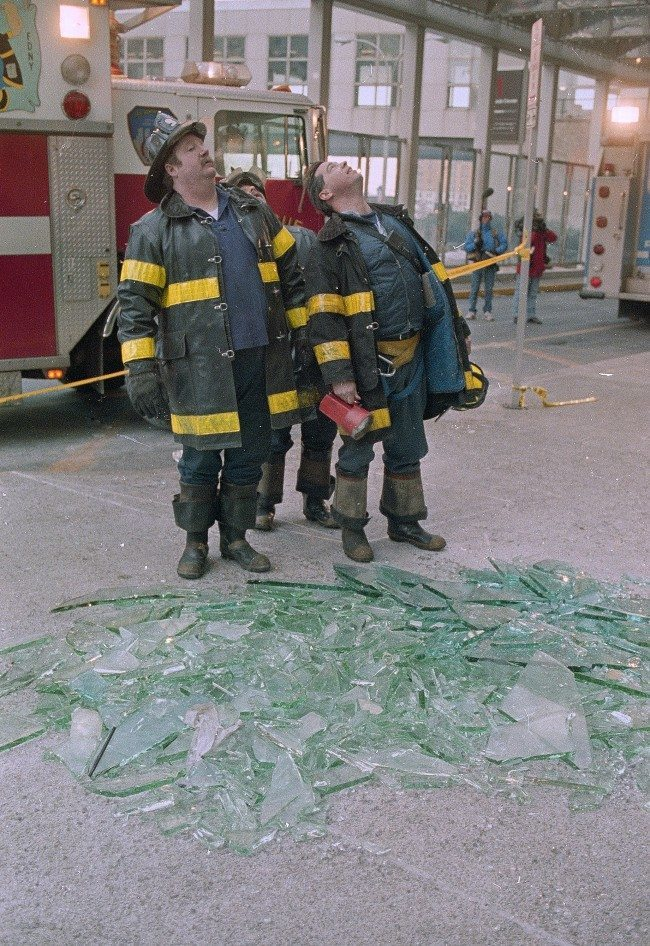 Three New York City firefighters look skyward in front of a pile of glass outside the twin towers of New York's World Trade Center, Feb. 27, 1993. An explosion rocked the center yesterday, killing at least five and injuring hundreds.