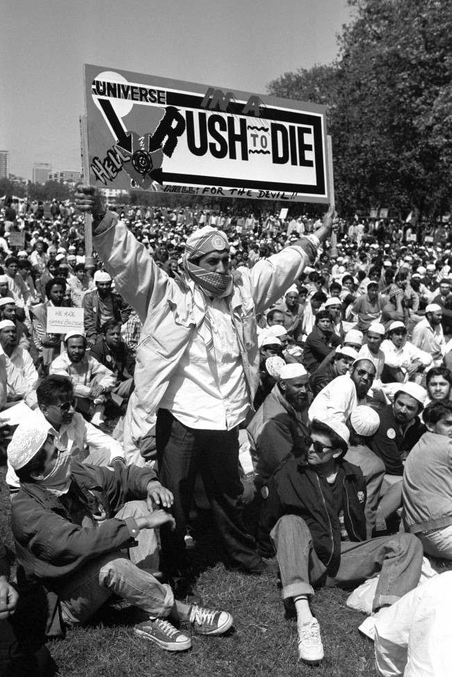 A Muslim holds aloft a dramatic banner in Hyde park, during a protest against Satanic Verses author Salman Rushdie. Date: 27/05/1989