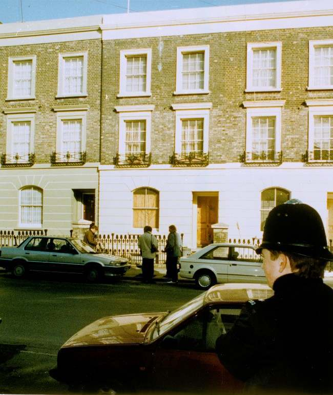 "Journalists stand outside the London residence of Salman Rushdie, author of ""The Satanic Verses,"" as a London policeman, foreground, watches from across the street, Feb. 16, 1989. Rushdie is presently in hiding under armed guard after Iran placed a 2.6 million dollar bounty on his head. Date: 16/02/1989"