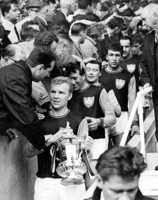 Soccer - FA Cup - Final - West Ham United v Preston North End West Ham United captain Bobby Moore carries the FA Cup down the steps after his team's 3-2 victory, followed by teammates (top to bottom) Ken Brown, Johnny Byrne, Peter Brabrook, Eddie Bovington and Geoff Hurst NULL Date: 02/05/1964