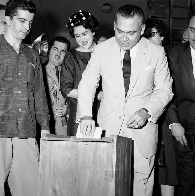 Placing his marked ballot in the ballot box is Cuba's President Fulgencio Batista as his wife, Marta, watches at left in Havana, Cuba, on Nov. 3, 1958. Polling places were guarded heavily. Havana was tense in face of threat of violence by Fidel Castro's rebels. Voting was light during day but a rush to vote is expected just before polls close.