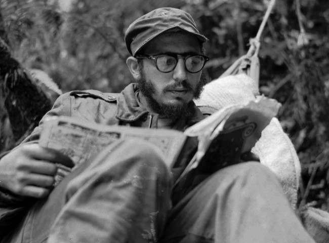 Cuban guerrilla leader Fidel Castro does some reading while at his rebel base in Cuba's Sierra Maestra mountains in this 1957 photo.