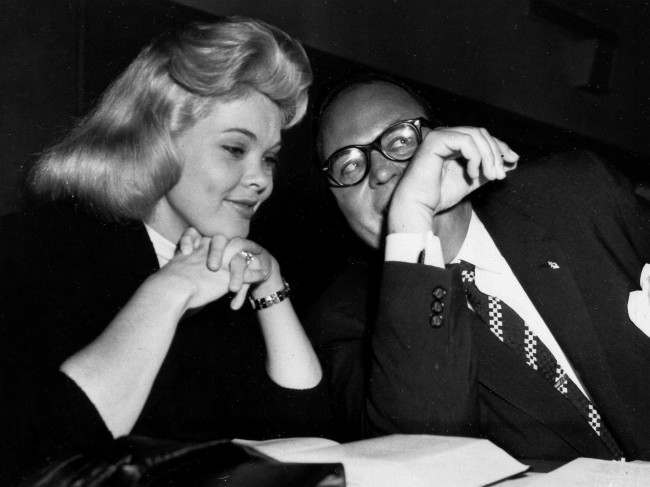 Burlesque dancer Candy Barr, left, smiles prettily as her attorney, Lester May, whispers to her at the defense table at the opening of her trial, Feb. 10, 1958, Dallas, Texas. The dancer is charged with illegal possession of narcotics