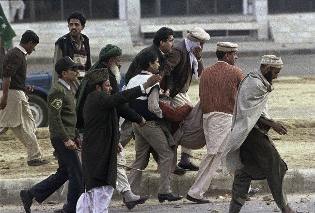 A Protester injured by police is carried away after a protest against the U.S. publication of Salman Rushdie's book. The Satanic Verses, turned violent, Sunday, Feb. 12, 1989 in Islamabad. A few thousand protesters marched on the American center where police had surrounded the area. At least five people were killed and fifty-five wounded when police used live rounds to try and stop the people attacking the center.