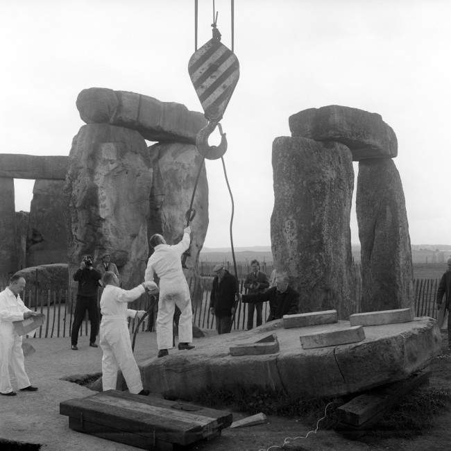 The hook of a crane is attached to the 25 tonne stone No.23 in the outer circle at Stonehenge. The stone, which fell over in 1963, was lifted clear by the crane and put into a timber cradle until its re-erection.