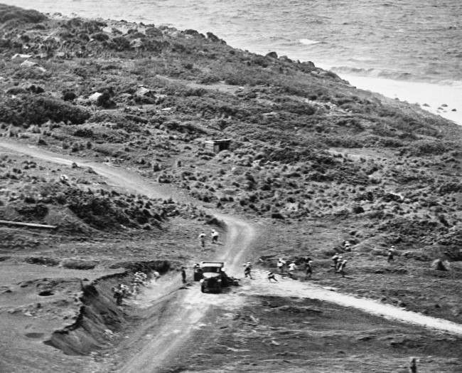 Near a truck on an Iwo Jima road in Japan on Feb. 20, 1945, Jap soldiers with field packs scatter for cover, as an American plane comes in low to strafe the enemy during pre-invasion softening-up. Japs at left dive into a gully; those at right head for a ravine; and others hide under the truck.