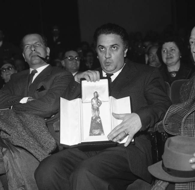 "Top Italian film director Federico Fellini sits holding the ""Chaplin d''Oro'"" (Golden Chaplin), a statuette representing Charlie Chaplin, in a Rome theatre at night on Feb. 21, 1960. He received this award for his latest film ""La Dolce Vita"" (The Sweet Life) from the movie association ""Charlie Chaplin"" which is composed chiefly of movie critics. ""La Dolce Vita"", although criticized by the church and Christian organizations, is in this moment the biggest movie success in Italy. The film was released only a few weeks ago. It runs more than 3 hours and attacks high society life in the Italian capital. (AP Photo/Ivan Crosoenco)"