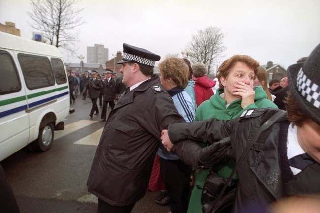 ANGUISH SHOWS ON THE FACE OF A YOUNG WOMAN BEHIND POLICE BARRIERS AS THE CONVOY CARRYING THE TWO-TEN-YEAR OLDS CHARGED WITH THE MURDER OF JAMES BULGER LEAVES SOUTH SEFTON MAGISTRATES COURT. 3/4 OF PEOPLE GASPING BEHIND THE BLUE LINE AS THE VAN PASSES BY.  Date: 22/02/1993