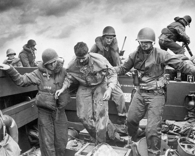 Wounded when Jap fire made a direct hit on an Amtrac, a Marine is transferred by Coast Guardsmen to a landing craft off the flaming shore of Iwo Jima, Japan on D-Day on Feb. 28, 1945.