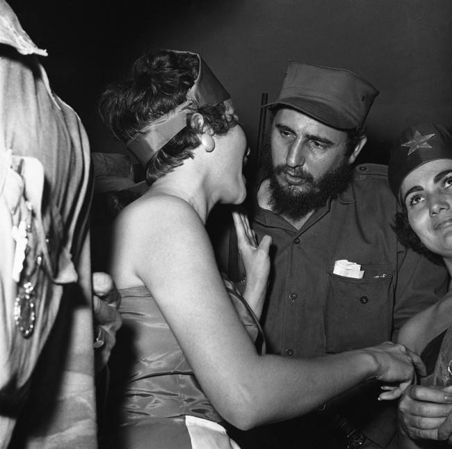 Pretty girls usually show up to greet victorious heroes and Fidel Castro head of Cuba?s Revolutionary forces was accorded the full treatment when he arrived at Camp Columbia, military headquarters in Havana on Jan. 8, 1959. Here at the reception center a girl dressed in the red and black colors of the 26th July Movement rushes up to greet Cuba?s newest hero.