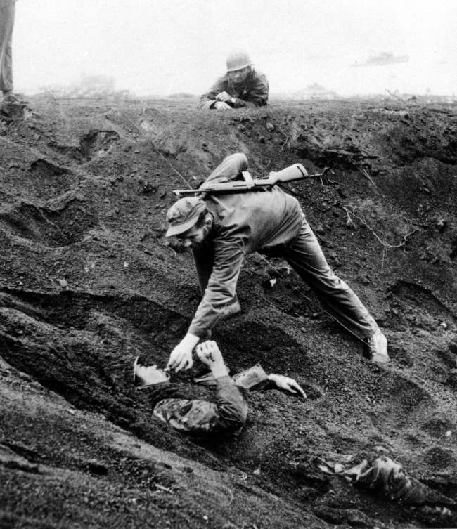 A U.S. Marine approaches a Japanese soldier on Iwo Jima, Japan, on March 16, 1945 during World War II. The Japanese soldier was buried for 1 1/2 days in this shell hole playing dead and ready with a live grenade inches away from his hand. The Marines feared he might be further booby trapped underneath his body after knocking the grenade to the bottom of the shell hole. Promising no resistance, the prisoner is given a cigarette that he asked for and was dragged free from the hole.