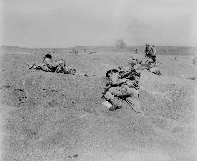 Two U.S. Marines, slumped in death, lie where they fell on Iwo Jima, among the first victims of Japanese gunfire as the American conquest of the strategic Japanese Volcano Island begins on Feb. 19, 1945 during World War II.