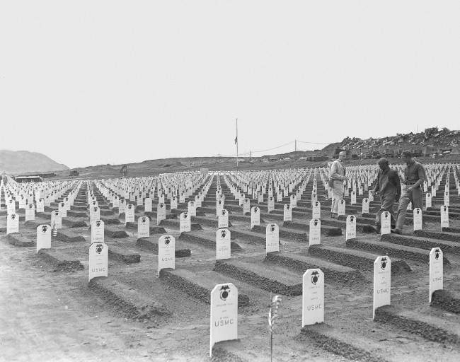 White markers designate the final resting place for hundreds of Third and Fourth Marine Division fighters, who died during invasion of Iwo Jima in World War II, in this cemetery located near the beach where the U.S. Marines first established a beachhead, April 1945. In the background, an American flag flies at half staff in tribute to the late President Franklin D. Roosevelt, who died in Warm Springs, Ga., on April 12.