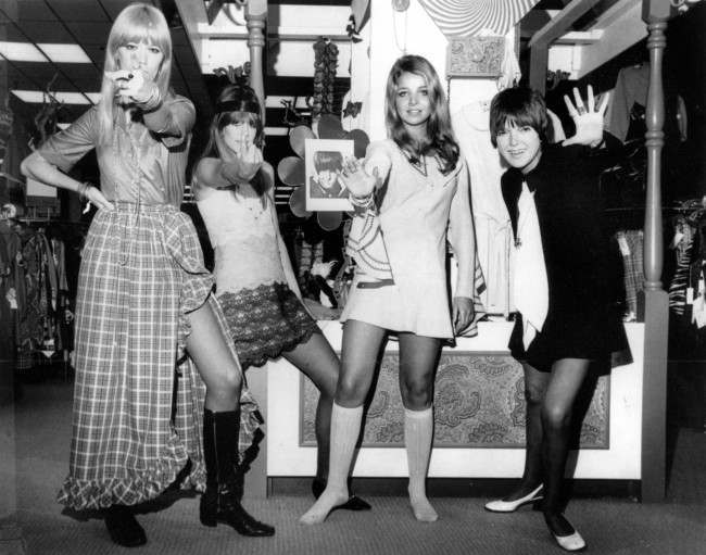 Mary Quant waves as she poses with models  on Oct. 25, 1968. The models, from left, are, Amanda Tear, Rory Davis and Penny Yates. (AP Photo)