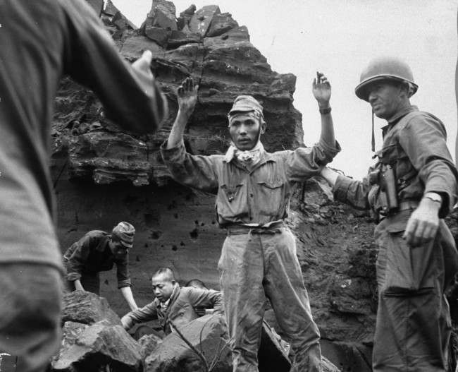 With his hands in the air, the first of 20 Japanese emerges from an Iwo Jima cave on April 5, 1945. The group had been hiding for several days.