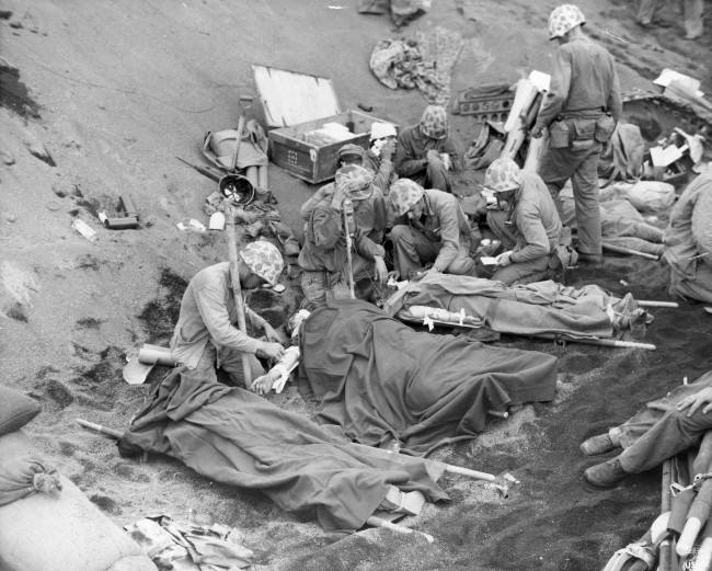 U.S. Navy doctors and medical corpsmen treat wounded U.S. Marines at an aid station established in a gully on Iwo Jima in the Pacific, Japan, on March 6, 1945 during World War II. Blood plasma and whole blood is administered from supplies flown from the west coast of the U.S.