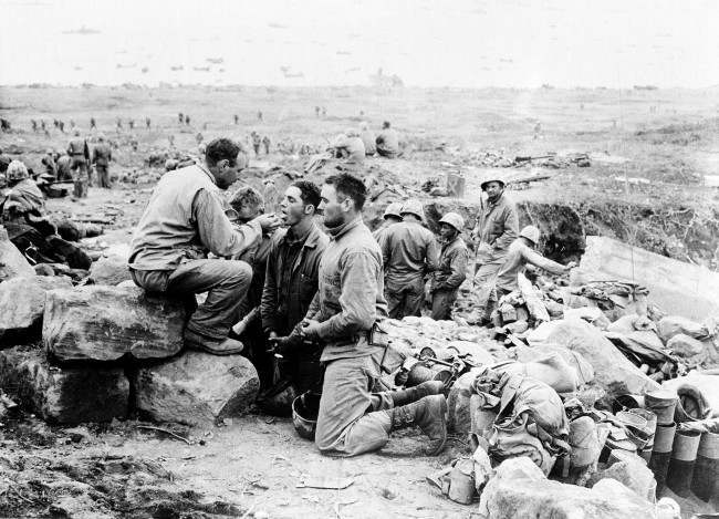U.S. Marines receive communion from a Marine chaplain on Iwo Jima, the largest of the Japanese Volcano Islands, on March 3, 1945 during World War II.