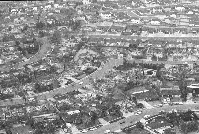 This aerial view shows charred rubble that marks remains of rows of homes destroyed by massive wild fires in north San Bernardino, Ca., Tuesday morning Nov. 25, 1980. Some homes were left virtually untouched by the flames, upper and lower right, but row after row of other homes, numbering hundreds, burned to the ground in the fire that started Monday.