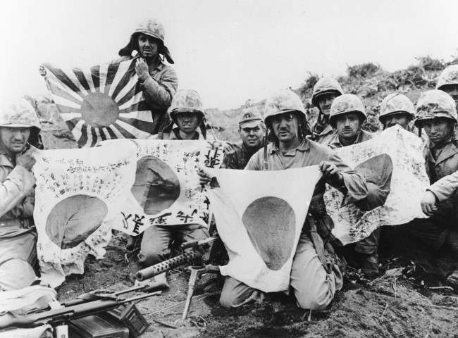 U.S. Marines of the 5th Division pose with captured Japanese battle flags, at Iwo Jima, on March 2, 1945.