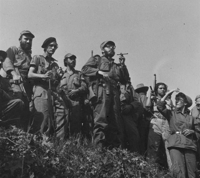 Soldiers of Rebel Chief Fidel Castro take positions on road bank as the revolutionary leader makes a roadside appearance a few miles from there January 7, 1959, as his columns travel toward Havana where a big welcome is expected tomorrow.
