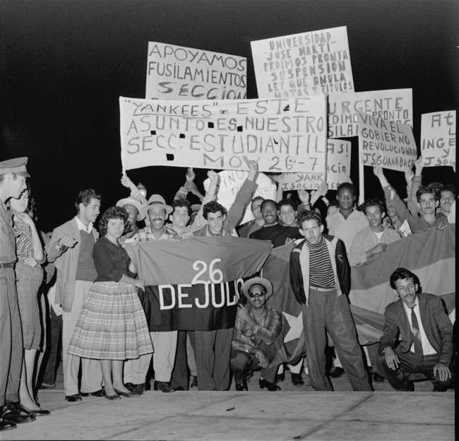 Students among crowd demonstrating in front of the presidential palace January 16, 1959, carry signs backing the rebel provisional government. Some of signs support executions which followed former dictator Fulgencio Batista's fall from power and victory of rebel leader Fidel Castro's forces; others say that what is happening in Cuba is Cuba's business.