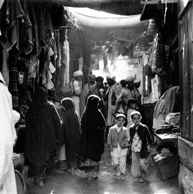 Afghan boys, men, and women, who have bare feet and wear long outer garments called an abaya or chador, shop at a market place in Kabul, Afghanistan, in May 1964.