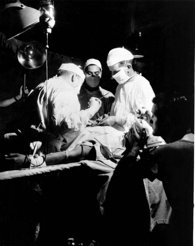 While a U.S. corpsman administers ether, Navy doctors operate to remove shrapnel from the abdomen of a wounded leatherneck at the Fourth Marine Division evacuation hospital in Iwo Jima, Japan, on March 14, 1945. The makeshift operating room is at an abandoned Japanese dugout several thousand yards from the front lines in World War II.
