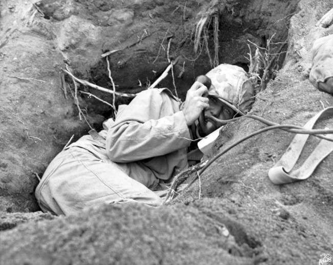 This is a March, 1945 photo of a U.S. Marine communicator, burrowed in a shallow foxhole, calling for artillery support to silence enemy mortars in Iwo Jima, Japan, during World War II.