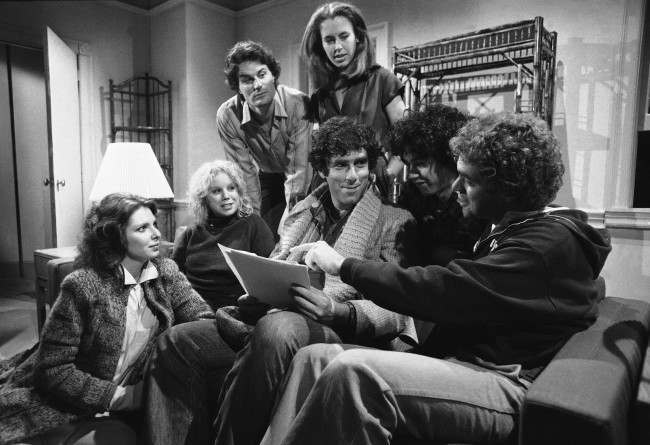 "Elliot Gould holds the script as he rehearses with the new cast of ""Saturday Night Live"" in New York, Nov. 13, 1980. They will make their debut with guest host Gould on November 15. From left: Ann Risley, Denny Dillon, Charles Rocket, Gail Matthius, Gilbert Gottfried and Joe Piscopo."