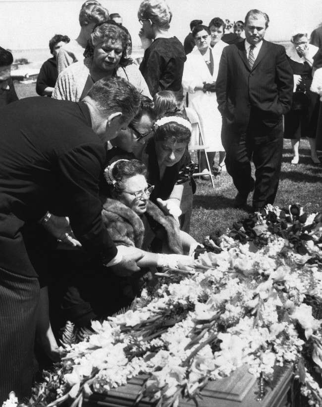 Grief - stricken Mrs. Alice Cochran is comforted by relatives as she weeps over the casket of her son, Rock and Roll singer Eddie Cochran, at his funeral at Forest Lawn Memorial Park in Los Angeles on April 25, 1960. Cochran was killed in an auto crash in England on April 17. Standing behind the group at the casket is Mrs. Concepcion Valens, whose son, singer Richie Valens, died in a crash last year. (AP Photo)