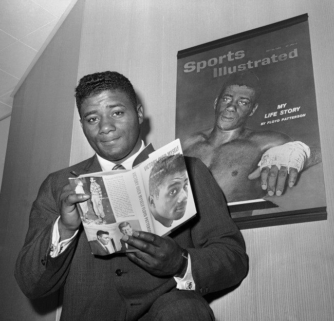 "Heavyweight champion Floyd Patterson holds up a copy of his new book, ""Victory over myself,"" during press conference in New York on May 23, 1962. He said his title fight against Sonny Liston will be held in Chicago in mid-September ""Unless something comes up."" Patterson, who has been in training for some time, said he probably would go to Chicago a month before the fight."