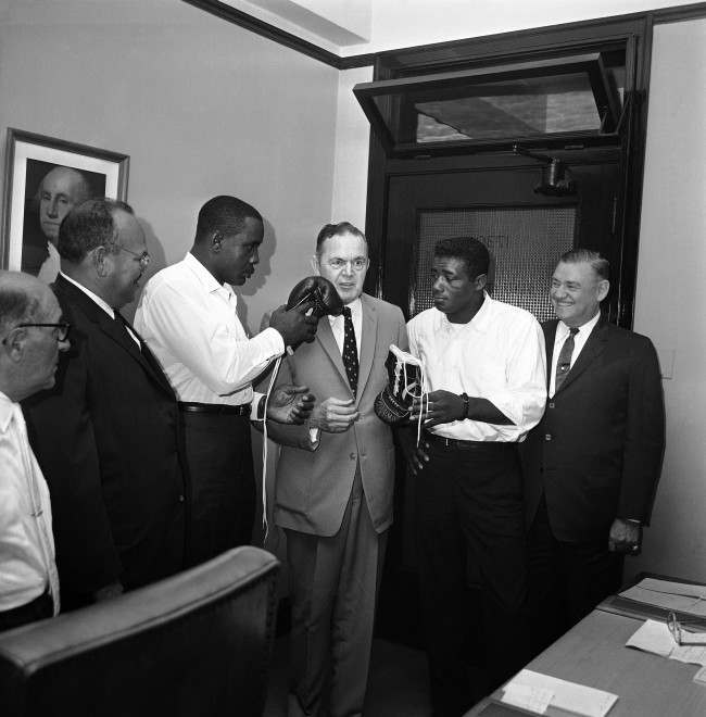 Joseph Triner, center, chairman of the Illinois Athletic Commission, gets feel of glove on his face when challenger Sonny Liston, left, and Champion Floyd Patterson, right, argued about use of gloves in his office in Chicago, Sept. 17, 1962. Liston wants to wear a glove made in Chicago when he meets Patterson in ring on September 25, for heavyweight championship. Patterson says he is partial to a glove manufactured in New York. Commission took the point under advisement.