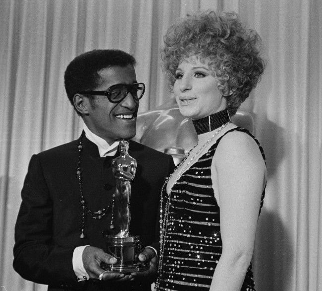 "Barbra Streisand with Sammy Davis, Jr., who accepted the Oscar for for Leslie Bricusse for ""Doctor Dolittle,"" April 10, 1968 (AP Photo)"