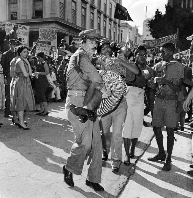 Rescue workers carry a woman to a first aid station after she fainted in the jam packed mob awaiting appearance of Fidel Castro in front of the Presidential Palace in Havana, Jan. 21, 1959. More than a score fainted in the area near the speakers stand as a hot sun beat down.