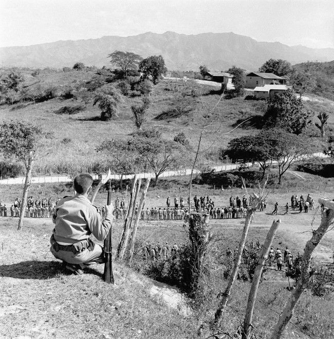 Armed teenage rebel soldier stands guard on hill overlooking training field for rebel troops of Fidel Castro, Jan. 19, 1956. Large portion of about 1,000 new recruits are in formation below. A few of these men have seen combat in fight to overthrow the Batista government. Training camp is near Santiago in Oriente province, birthplace of the revolution in Cuba.
