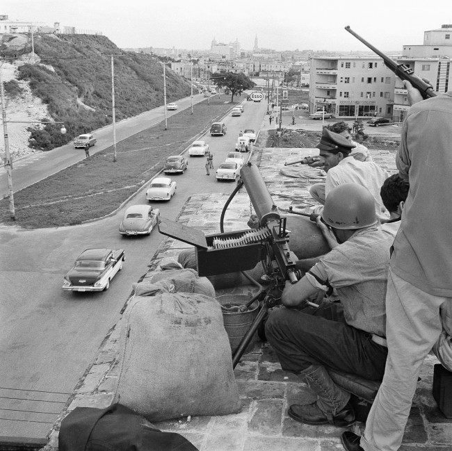 Supporters of the Revolutionary government of Cuba man a machine gun post overlooking one of the main streets, Zapata Avenue, into the heart of the city (background) in Havana, Jan. 4, 1959. Tension eased in the city somewhat but Fidel Castro's supporters kept a close armed watch on the city.