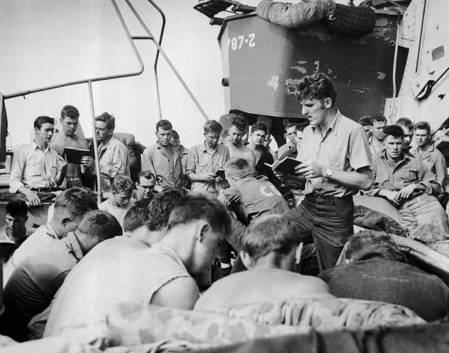 Coast Guardsman Charles R. Roth (right center), PHM/2c, of 296 prospect St., Lawrence, Mass., leads the singing of hymns on an LST headed for Iwo Jima, on the day before the invasion Feb. 26, 1945.