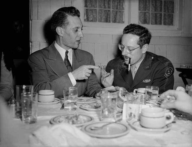 Associated Press photographer Joe Rosenthal, right, whose Iwo Jima Mount Suribachi flag-raising picture has made pictorial history, and Howard L. Kany, left, Washington news photo editor, enjoy a dinner in Joe's honor, given during his visit to Washington by the AP Washington NewsPhoto staff at the Purple Iris Inn, March 30, 1945. Thirty-seven staffers, their wives, friends and Marines attended.