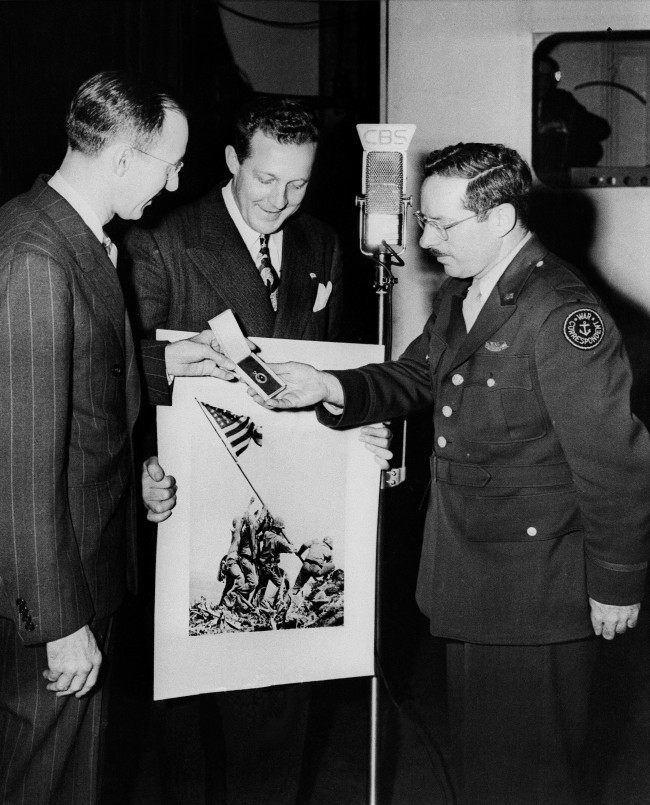 "Joe Rosenthal, Associated Press photographer whose shot of the flag raising on Iwo Jima has become a classic, received further recognition when he was awarded the Graflex Diamond Award during an appearance on the ""We, The People"" television broadcast, April 1, 1945. From left to right: H.A. Schumacher, Vice President of the Former Graflex Corporation, who made the presentation on the air; Milo Boulton, emcee of the program, and Rosenthal. The twenty-sixth presentation, it was the first time that the Graflex Diamond Award has been made during the war."