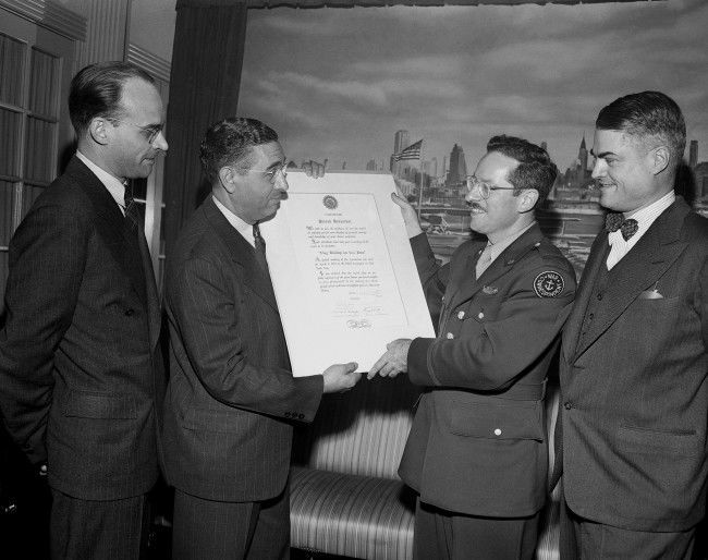 Joe Rosenthal, second from right, Associated Press staff photographer, receives a scroll from Joe Costa on behalf of the Press Photographers Association of New York in a ceremony commending him for his photo of the flag raising on Iwo Jima, in New York, April 4, 1945. Costa is president of the association.