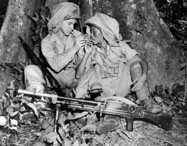 Corp. Rolf Krog, left, of St. Joseph, Mo., lights a cigarette for a Chinese soldier in the China-Burma-India theatre of operations on Oct. 14, 1943 where Chinese have been trained in use of American Army equipment for the past year. Mosquito netting in fastened to each helmet.