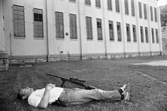 An unidentified sharpshooter at Brushy Mountain State Prison at Petros, Tennessee, June 11, 1977, takes a nap on the lawn in front of Cellblock after duty in the search for six escaped convicts. Hundreds of law officers search the mountains for the escapees, including James Earl Ray.