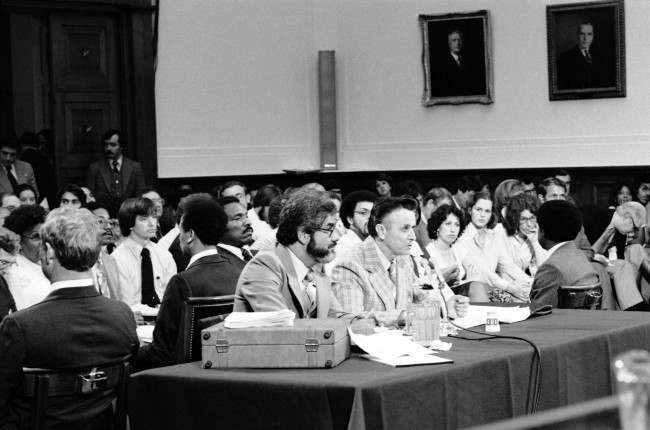 James Earl Ray sits with his attorney Mark Lane during testimony before the House Assassinations Committee in Washington, August 16, 1978. Federal marshals form a ring around ray and the attorney as they sit with their books to the table facing the audience.